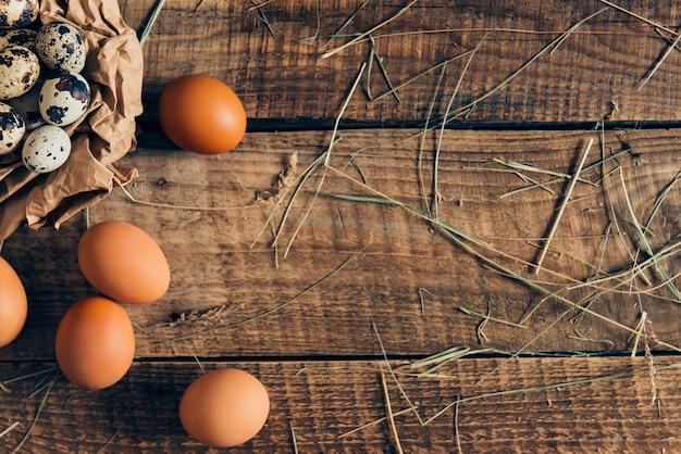 Frais et bio. vue de dessus des œufs de caille dans du papier brun froissé et des œufs bruns allongés sur une table rustique en bois