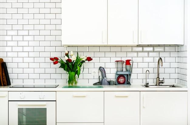 Frais bouquet de tulipes rouges et blanches sur la table de la cuisine. détail de l'intérieur de la maison, design.