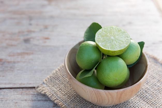 Frais branche de limes dans un bol en bois sur une vieille table en bois