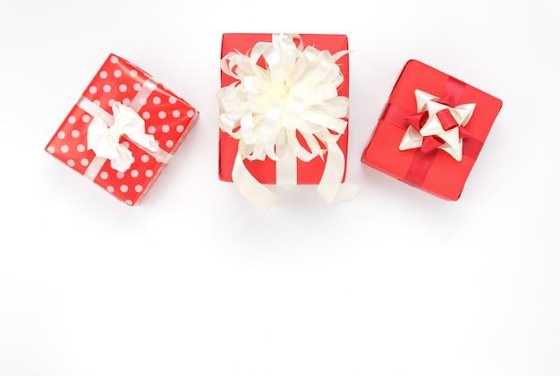 Frais généraux d'accessoires bonne année ou joyeux anniversaire ou concept de joyeux noël. boîte de cadeaux rouge de côté de mélange sur le fond blanc moderne au home studio de table. copie de police ou de texte créatif de conception d'espace.