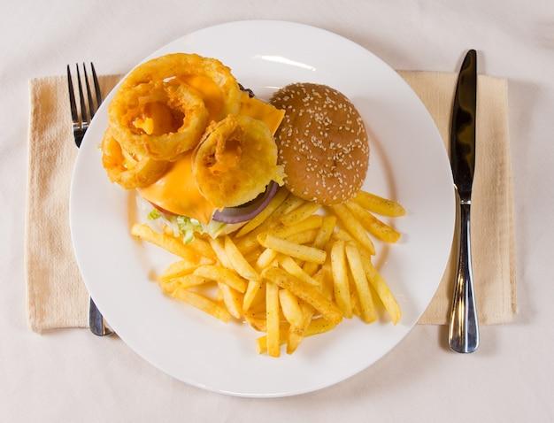 Frais généraux de gourmet cheeseburger et frites sur la plaque à la place
