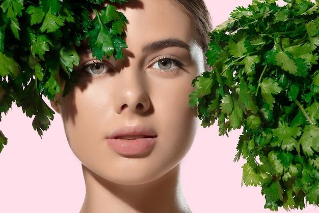 Frais. gros plan de la belle jeune femme avec des feuilles vertes sur son visage sur fond blanc.