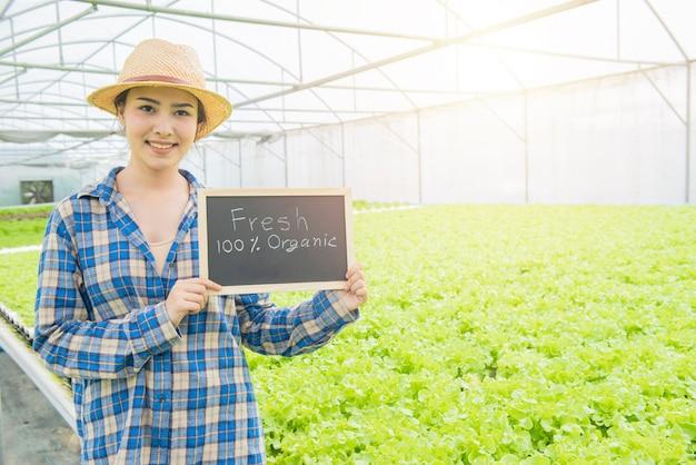 Frais de la main texte de la ferme dessiné sur le tableau noir en hydroponique bio les légumes frais produisent une boîte en bois dans la ferme de la pépinière de jardin à effet de serre.