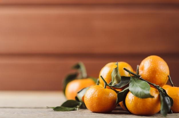 Frais petites mandarines juteuses avec des feuilles vertes dans un tas sur bois sombre