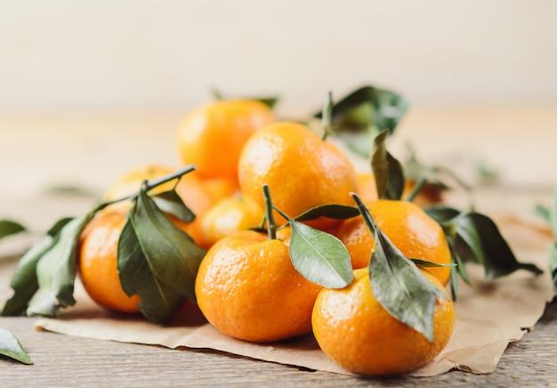 Frais petites mandarines juteuses avec des feuilles vertes en tas sur fond blanc en bois et papier kraft.