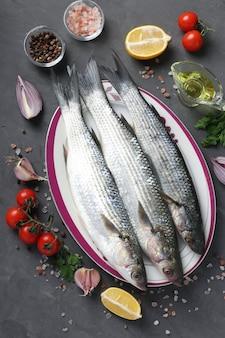 Frais prêts à cuire des rougets crus avec des ingrédients et des assaisonnements comme le persil, le citron, les tomates cerises, l'oignon rouge et l'huile d'olive sur une surface sombre