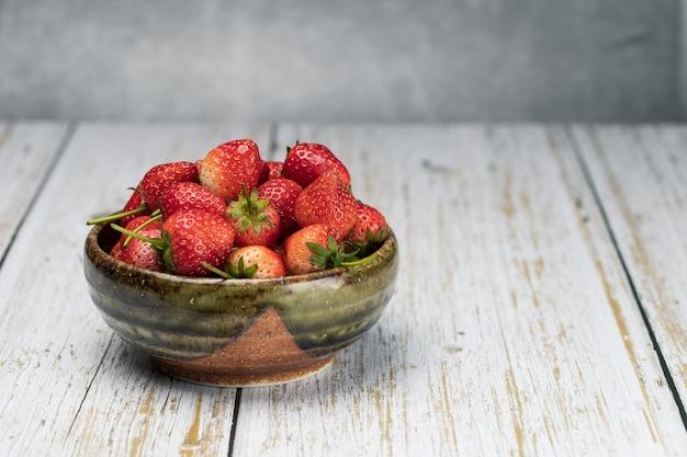La fraise dans l'assiette sur le plancher en bois blanc