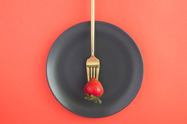 Une fraise sur une fourchette d'or dans la plaque noire au centre du fond rouge. vue de dessus. concept minimal de régime.