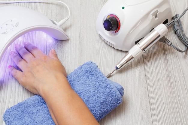 Fraise et lampe uv à led avec main de femme sur fond de bois gris. un ensemble d'outils cosmétiques pour la manucure de matériel professionnel. vue de dessus
