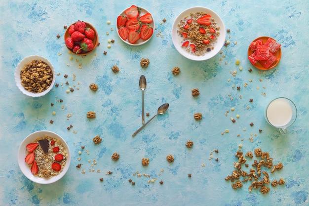 Fraise, muesli et délice turc sur une table turquoise. c'est l'heure du déjeuner. les cuillères montrent l'heure.