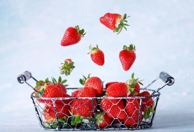 Fraises biologiques rouges crues en lévitation. fruits volants.