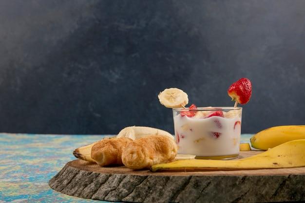 Fraises à la crème servies avec bananes et feuilletés