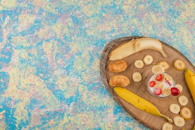 Fraises à la crème servies avec des bananes et des pâtisseries feuilletées, vue du dessus