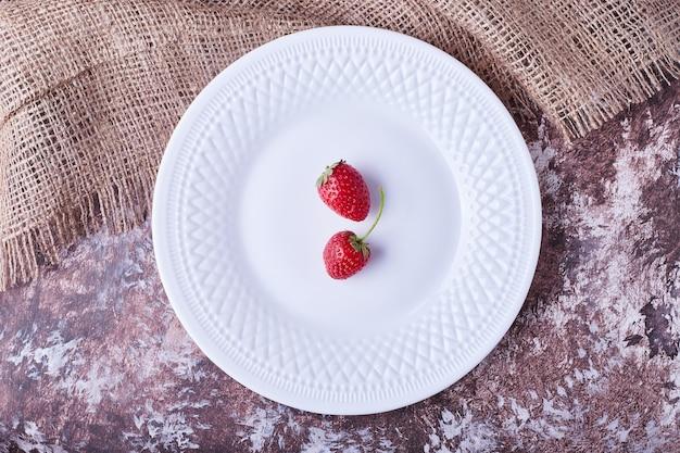 Fraises dans une assiette blanche, vue du dessus.