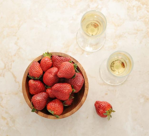 Fraises dans une assiette en bois et deux verres de champagne