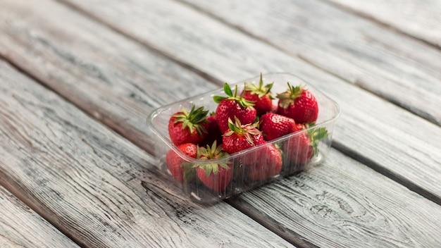 Fraises dans un récipient. baies sur fond en bois. fraises fraîches pour cocktail. suivre un régime nécessite des vitamines.
