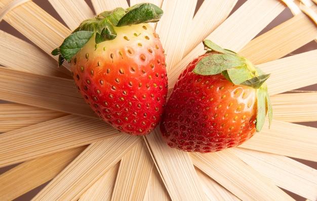 Fraises, deux belles fraises sur un panier de paille tressée, mise au point sélective.