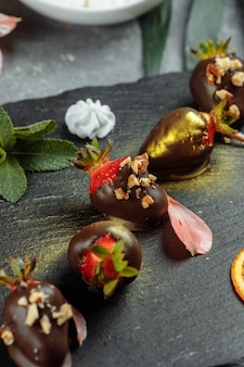 Fraises enrobées de chocolat frais sur un fond décoratif gris. concept pour la publicité du menu saisonnier d'été.