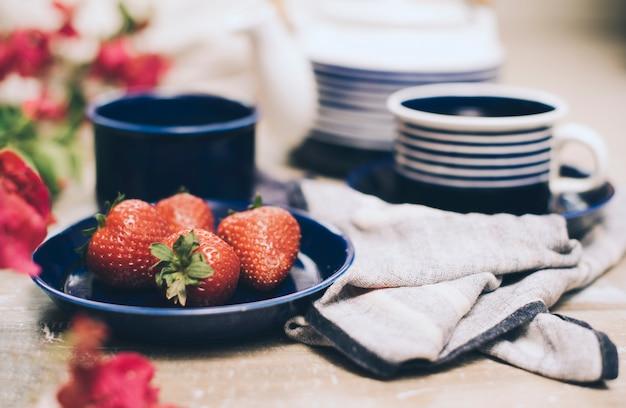 Fraises entières et thé flou mis sur la table