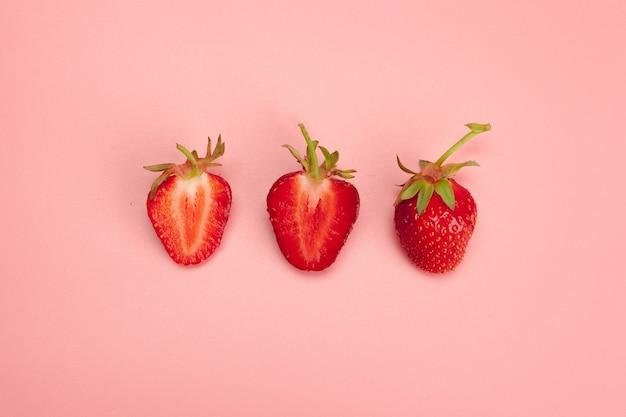 Fraises sur fond rose concept d'aliments biologiques frais
