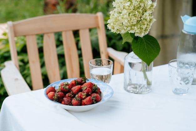 Fraises fraîches dans une assiette bouquet sur une table de jardin servie pour le petit-déjeuner