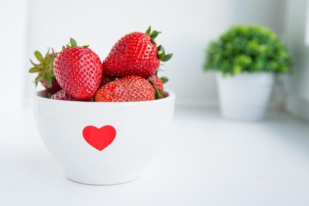 Fraises fraîches dans un bol blanc avec coeur rouge sur fond blanc close up avec copyspace