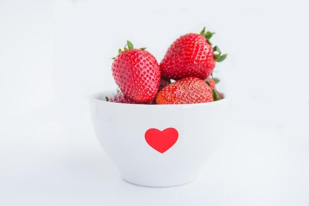 Fraises fraîches dans un bol blanc avec coeur rouge sur fond blanc se bouchent