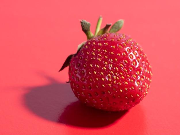 Fraises mûres juteuses lumineuses sur fond rouge. vue de face, alimentation saine, végétarisme