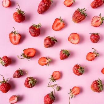 Fraises mûres rouges sur rose, poser à plat.
