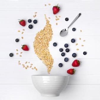 Fraises, myrtilles, pignons de pin et flocons d'avoine coulent dans un bol en céramique pour la cuisson de muesli ou de granola fait maison