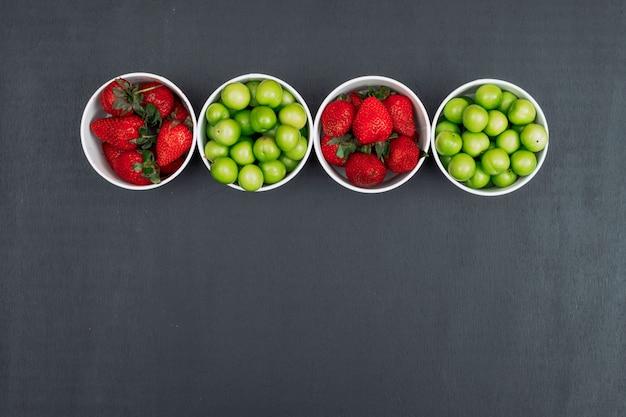 Fraises et prune cerise verte dans un bol en carton vue de dessus sur un espace de fond noir pour le texte