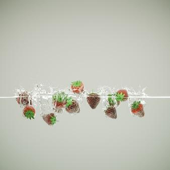 Des fraises qui tombent dans l'eau et créent des éclaboussures.