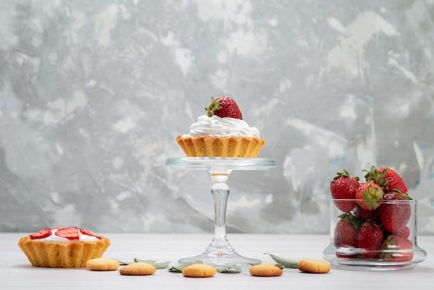 Fraises rouges fraîches moelleuses et délicieuses baies avec des gâteaux et des biscuits sur un bureau léger