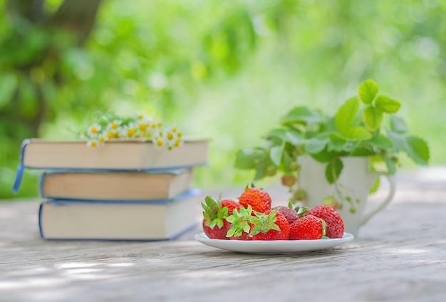 Fraises rouges et une pile de livres sur la table dans le jardin. concept de vacances d'été. concept d'aliments biologiques.