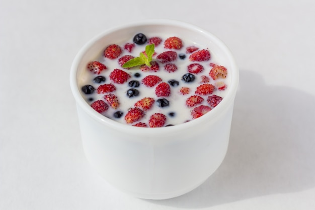 Fraises sauvages fraîches avec du lait dans une tasse blanche.