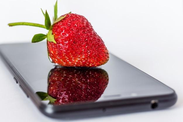 Les fraises se trouvent sur un téléphone mobile et se reflètent dans l'écran