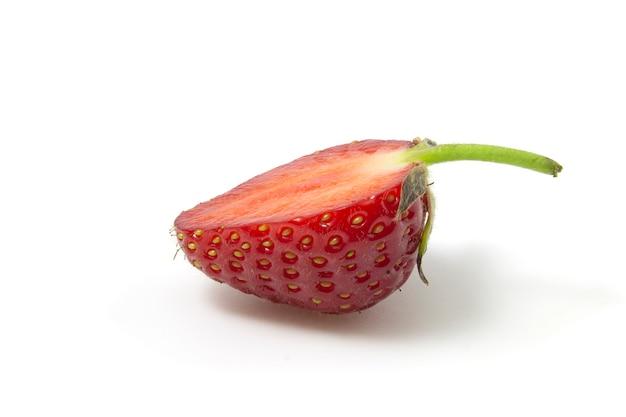 Les fraises en section se trouvent latéralement isolées sur un fond blanc. pleine concentration.