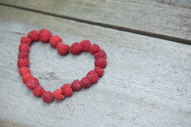 Framboises berry dans un coeur rouge sur fond de bois ancien