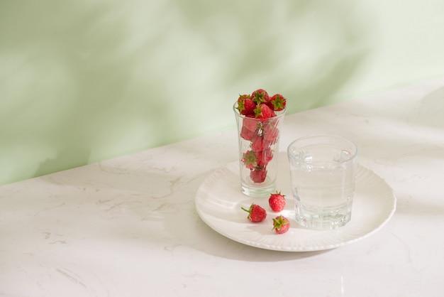 Framboises fraîches dans un bécher en verre isolé sur fond clair