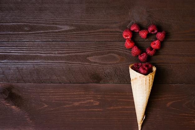 Framboises fraîches de jardin fait maison dans un cornet de crème glacée à la gaufre et un cœur de framboise sur un fond marron