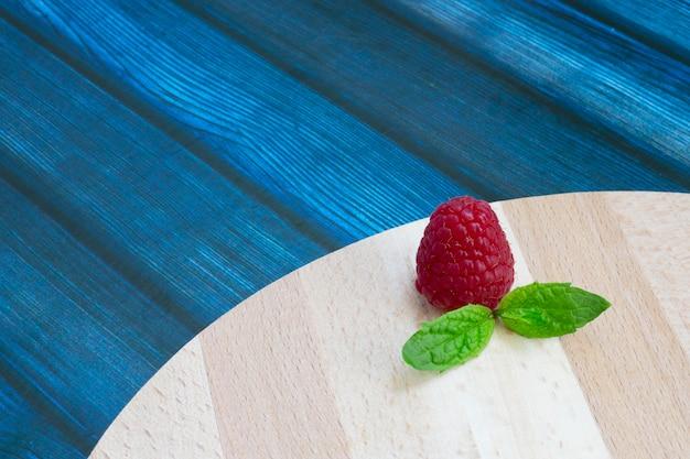 Framboises fraîches et menthe sur une table en bois. framboises rouges mûres et feuilles de menthe verte sur un support en bois