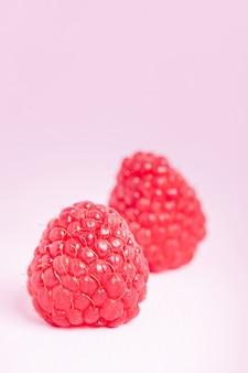 Framboises mûres crues avec feuille de menthe verte fraîche isolé sur fond pastel rose.