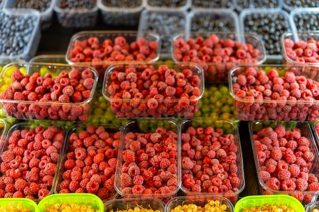 Framboises rouges juteuses vives dans un récipient en plastique