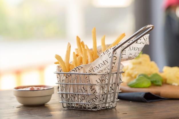 Français frites avec du ketchup sur fond en bois