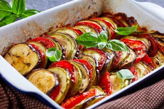 Français tian provençal, légumes en couches tranchées au four dans un plat allant au four sur une table en béton, close-up