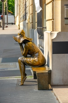 La france. une journée d'été ensoleillée dans les rues de paris. sculpture urbaine d'une fille sur un banc