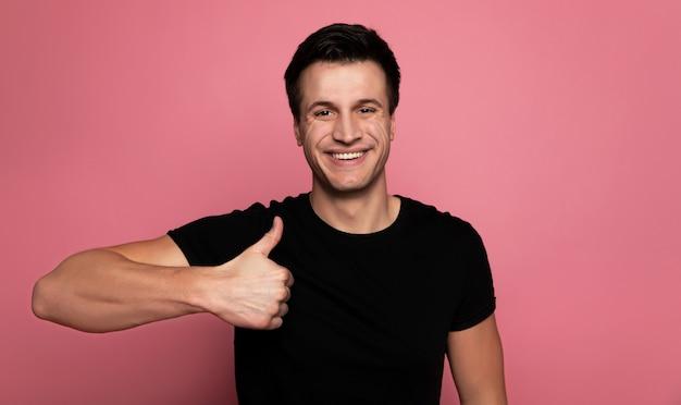Frapper comme. homme heureux dans un t-shirt noir, qui regarde la caméra avec un grand sourire et montrant les pouces vers le haut.