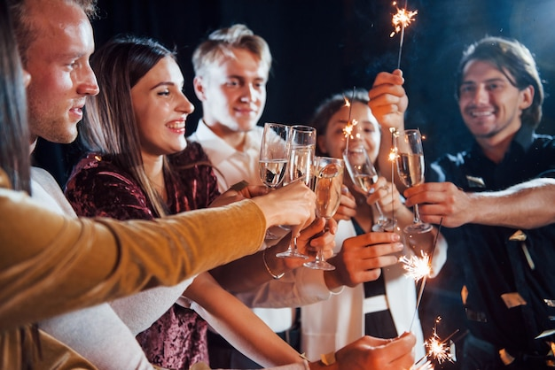 Frapper des verres. groupe d'amis joyeux célébrant le nouvel an à l'intérieur avec des boissons à la main.