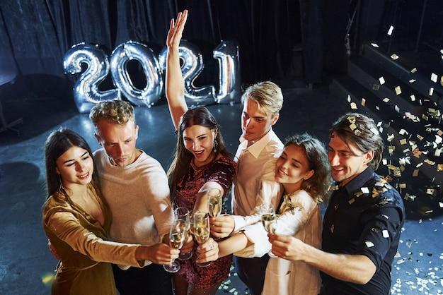 Frapper des verres. joyeux groupe de personnes avec des boissons à la main célébrant la nouvelle année 2021.