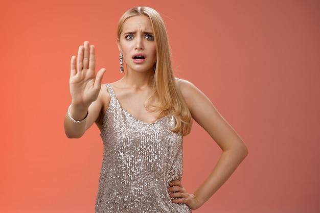 Freaked out mécontent gêné femme blonde insécurisée en robe argentée scintillante étendre la paume arrêter assez de geste de rejet d'interdiction gêné énervé discothèque homme collant ennuyeux, fond rouge.